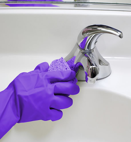 person cleaning sink with glove on
